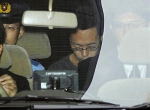 Tomohiro Kato, center, suspected of Sunday's deadly stabbing rampage, sits inside a car as he is transferred from a police station in Tokyo Tuesday, June 10, 2008.